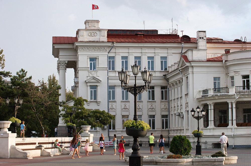 Turistas na praça em frente à Casa da Infância e Juventude (antiga Casa dos Pioneiros) em Sevastopol.