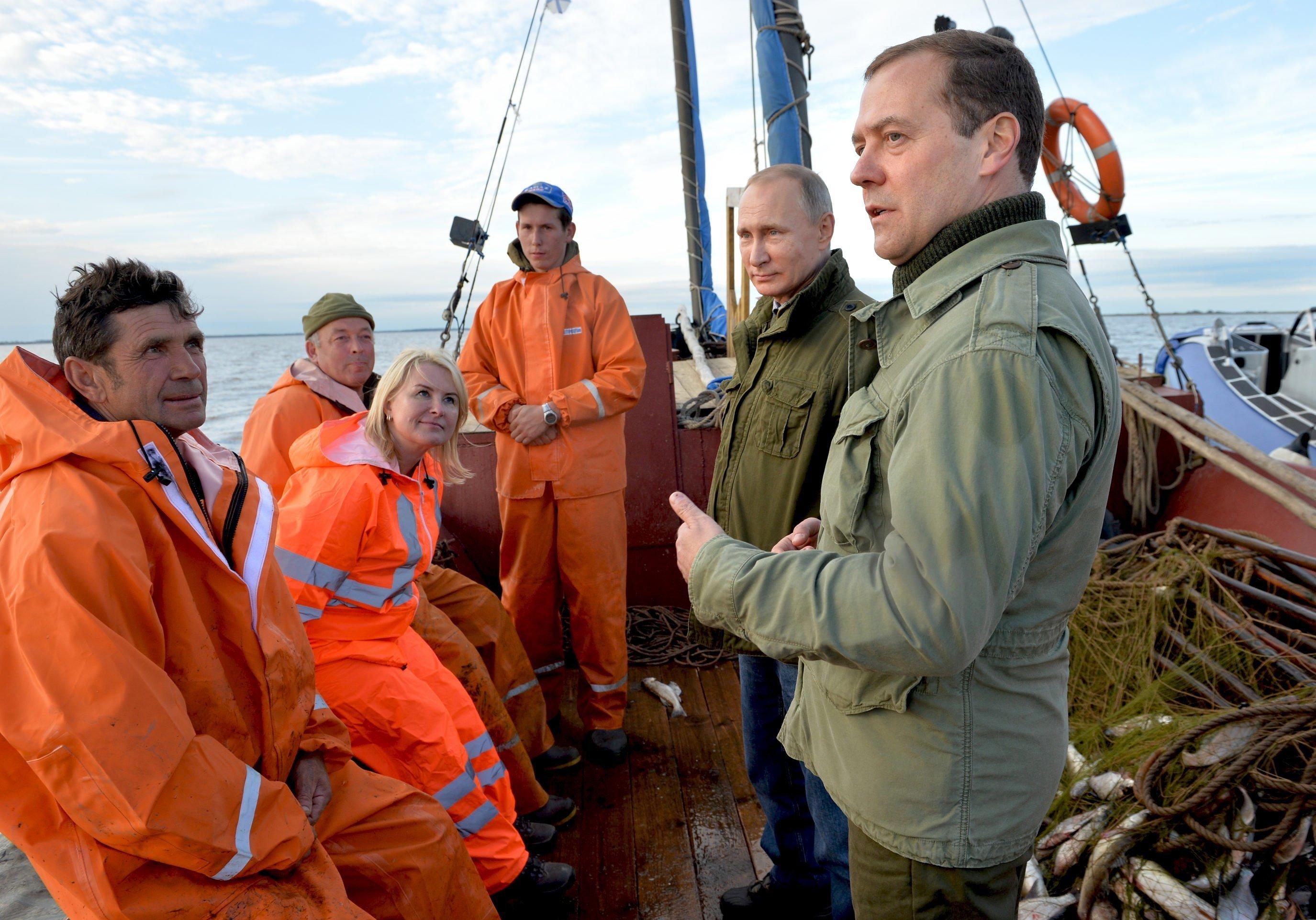 O presidente russo Vladimir Putin e o primeiro-ministro Dmitry Medvedev falam com pescadores durante um passeio de barco no lago Ilmen, Região de Novgorod, em 10 de setembro de 2016