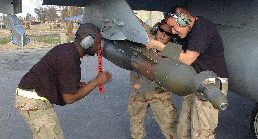Soldados americanos suspendem uma bomba da asa de um F-16, Iraque