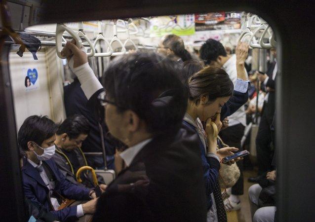 Uma mulher vendo seu celular no metrô em Tóquio, 12 de maio de 2015