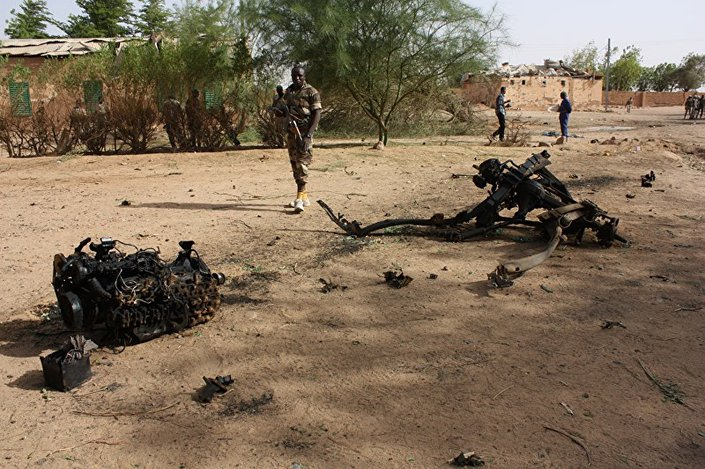 Esta foto de 23 de maio de 2013 mostra um grupo de soldados do Níger examinando o local de uma explosão suicida em uma instalação militar em Agadez