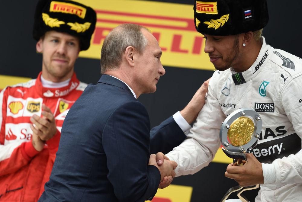 Presidente russo Vladimir Putin entrega a Taça Grand Prix da Rússia ao corredor de F1 Lewis Hamilton da equipe Mercedes