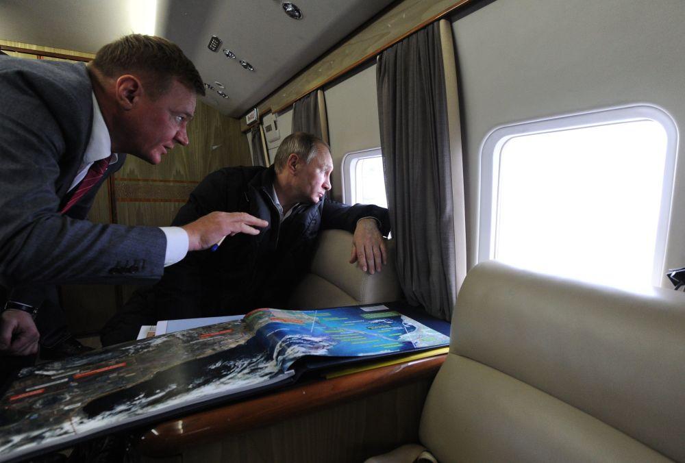 Chefe de Estado russo Vladimir Putin e o dirigente da Agência Rodoviária Federal (Rosavtodor) Roman Starovoit durante um voo sobre a passagem para transportes no estreito de Kerch, Crimeia, Rússia