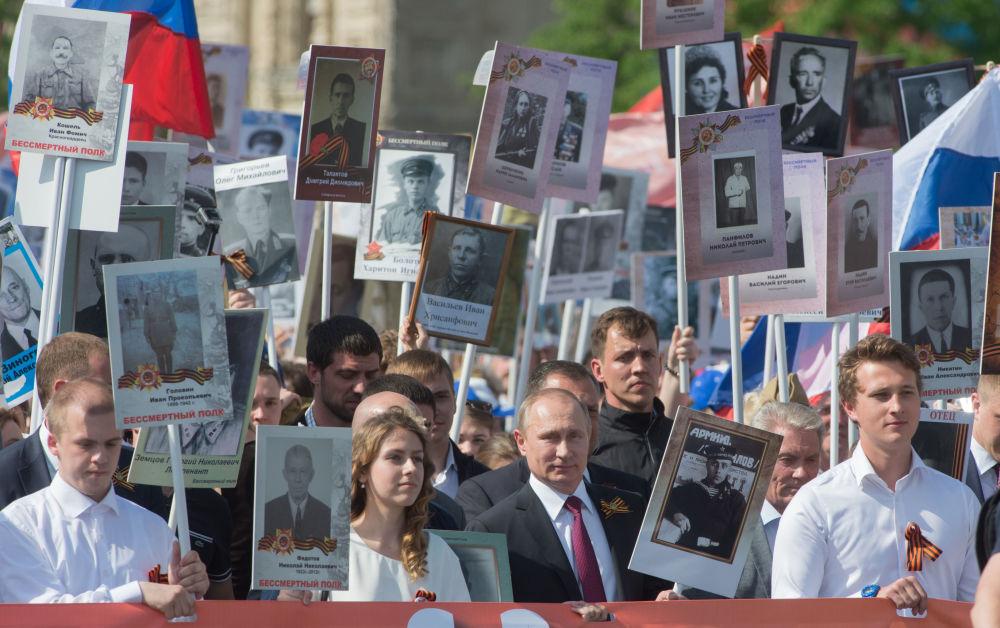 Presidente russo Vladimir Putin com retrato de seu pai, que combateu na Grande Guerra Patriótica, durante a ação patriótica Regimento Imortal na Praça Vermelha, Moscou, Rússia, 9 de maio de 2016
