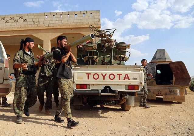 Forças curdas e árabes, aliados dos EUA, preparam um lançador de foguete móvel antes de se deslocar para Manbij, ocupada por terroristas do Daesh, em 23 de junho de 2016