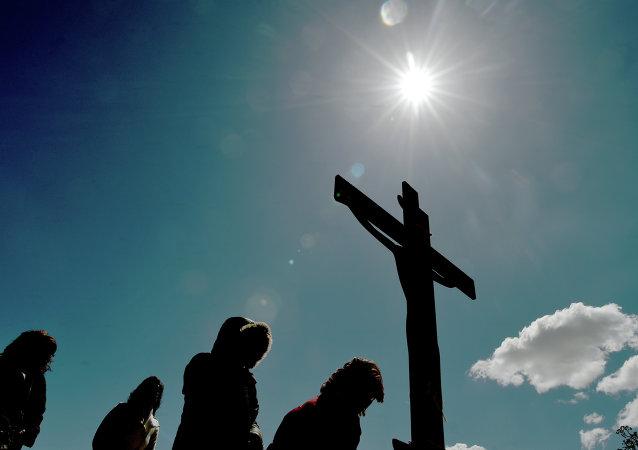 Peregrinos da Igreja Ortodoxa Grega ficam na frente de uma imagem de Jesus crucificado durante a marcação de Apokathelosis, a remoção do corpo de Cristo da cruz, em uma cerimônia na Igreja da Dormição da Virgem na Penteli, norte de Atenas, em 10 de abril de 2015