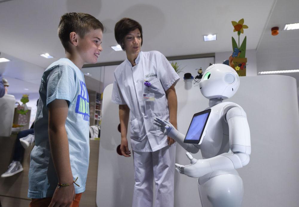 Um rapaz com robô Pepper em um hospital na Bélgica - o robô realiza a função de enfermeira. Ele pode ser programado para ajudar um paciente com necessidades específicas