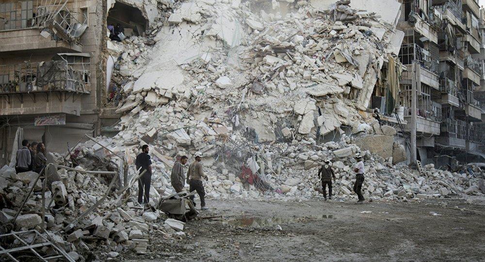Membros da Defesa Civil da Síria procuram vítimas entre os destroços do prédio destruído, depois de ataques aéreos no bairro de Qatarji, na cidade de Aleppo em 17 de outubro de 2016