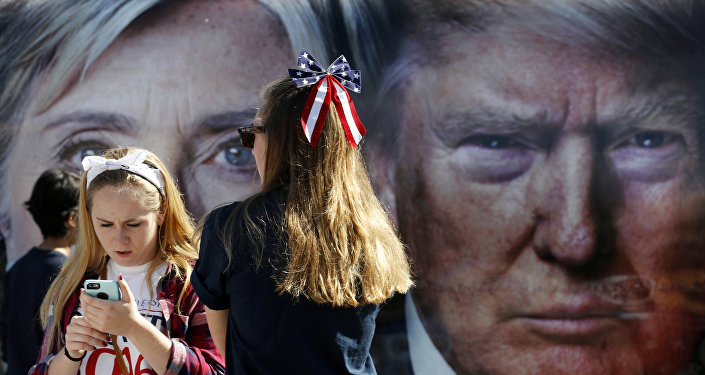 Pessoas aguardam ao lado de um ônibus, adornado com fotos dos candidatos à presidência dos EUA, Hillary Clinton e Donald Trump