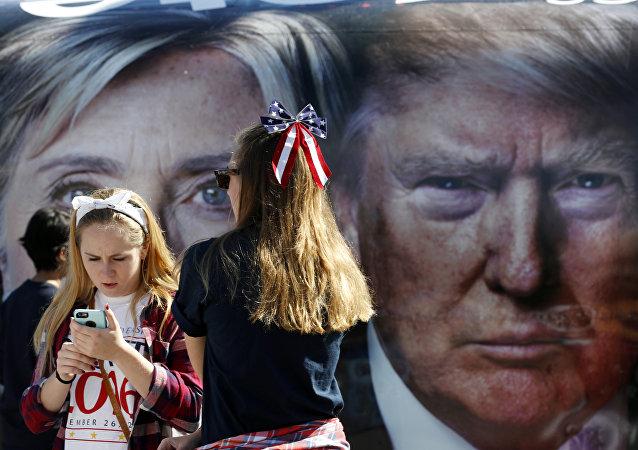 Pessoas aguardam ao lado de um ônibus, adornado com fotos dos candidatos à presidência dos EUA, Hillary Clinton e Donald Trump, antes do seu primeiro debate