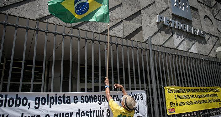 Manifestante com bandeira do Brasil na sede da Petrobras