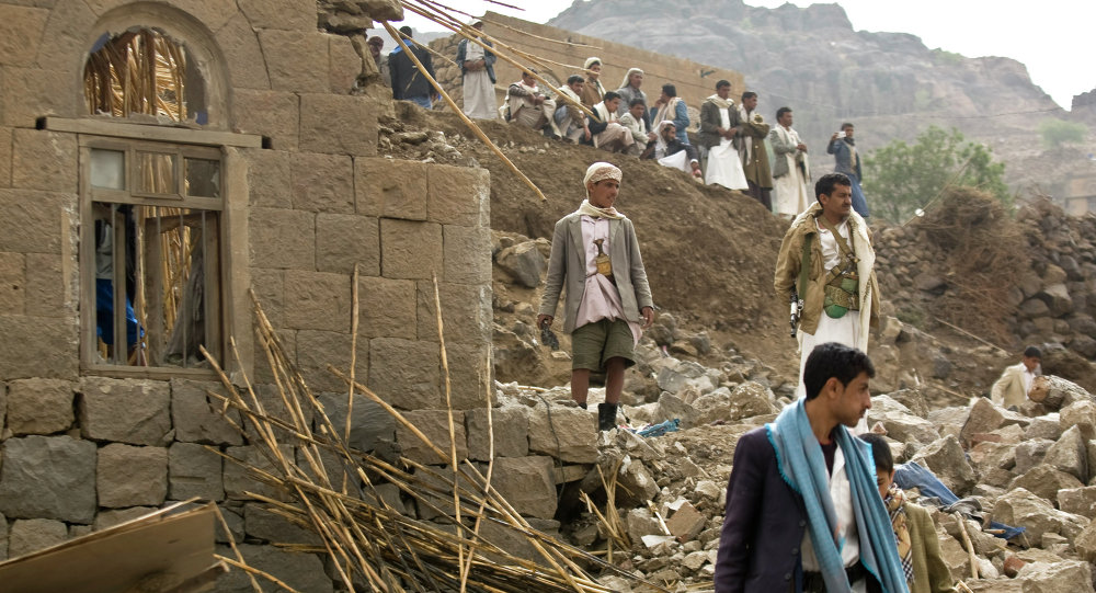 Iemenitas andam sobre destroços de casas destruidas pelos bombardeios sauditas perto da capital Sanaa