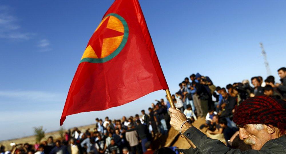 Curdo com bandeira durante funeral pelos mortos em combate pela cidade de Kobani, 23.10.2014 (Arquivo)