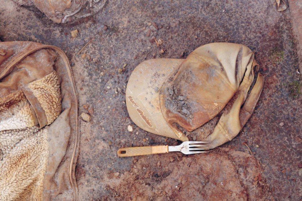 Um boné e um garfo abandonados sobre o chão de terra, fragmentos de vida deixados para trás na lama após o rompimento da barragem