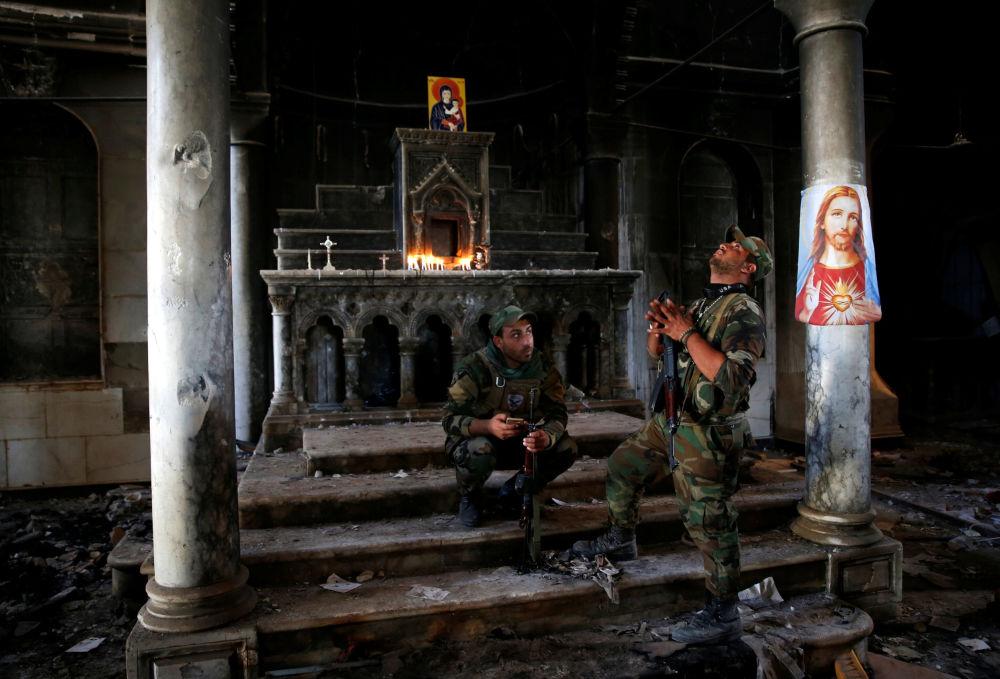 Soldados cristãos iraquianos em uma igreja libertada dos terroristas na periferia da cidade de Mossul