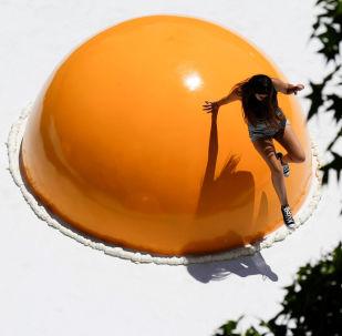 Девушка спрыгивает с инсталляции яичницы, представленной в рамках фестиваля городского искусства Hecho en Casa в пригороде Сантьяго, Чили
