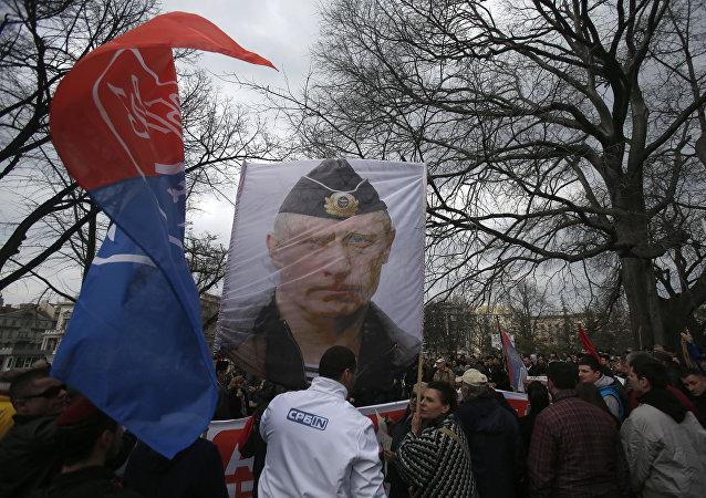 Manifestantes carregam imagem de Vladimir Putin, presidente da Rússia, durante um protesto contra a OTAN em Belgrado, Sérvia