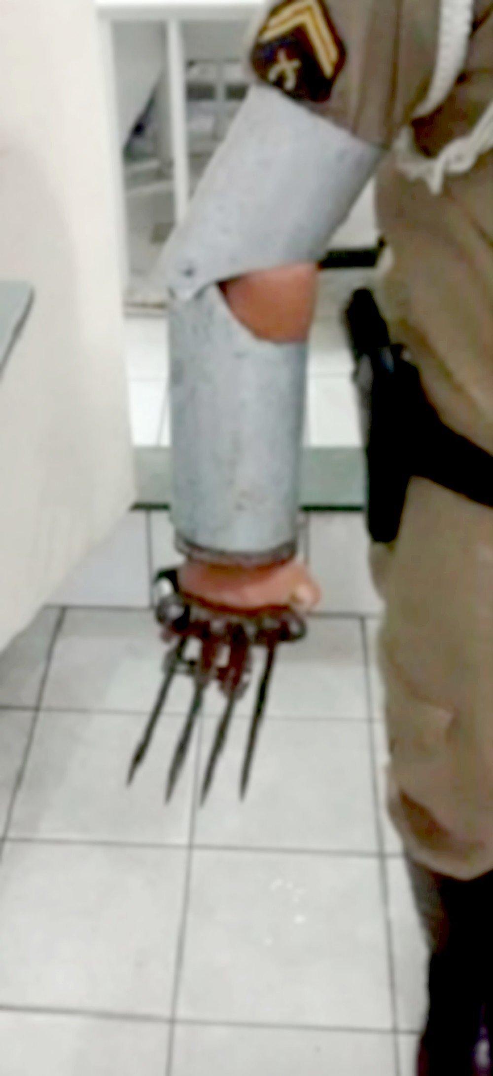 Um policial demostra como a armadura artesanal com as garras foi usada