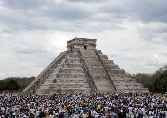Turistas reunem-se junto ao Templo de Kukulcán mexicano, na cidade legendária de Chichén Itzá,