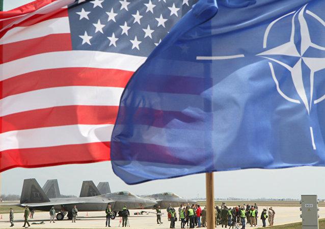 Bandeiras dos EUA e da OTAN em frente dos caças F-22 Raptor  da Força Aérea norte-americana, na Lituânia