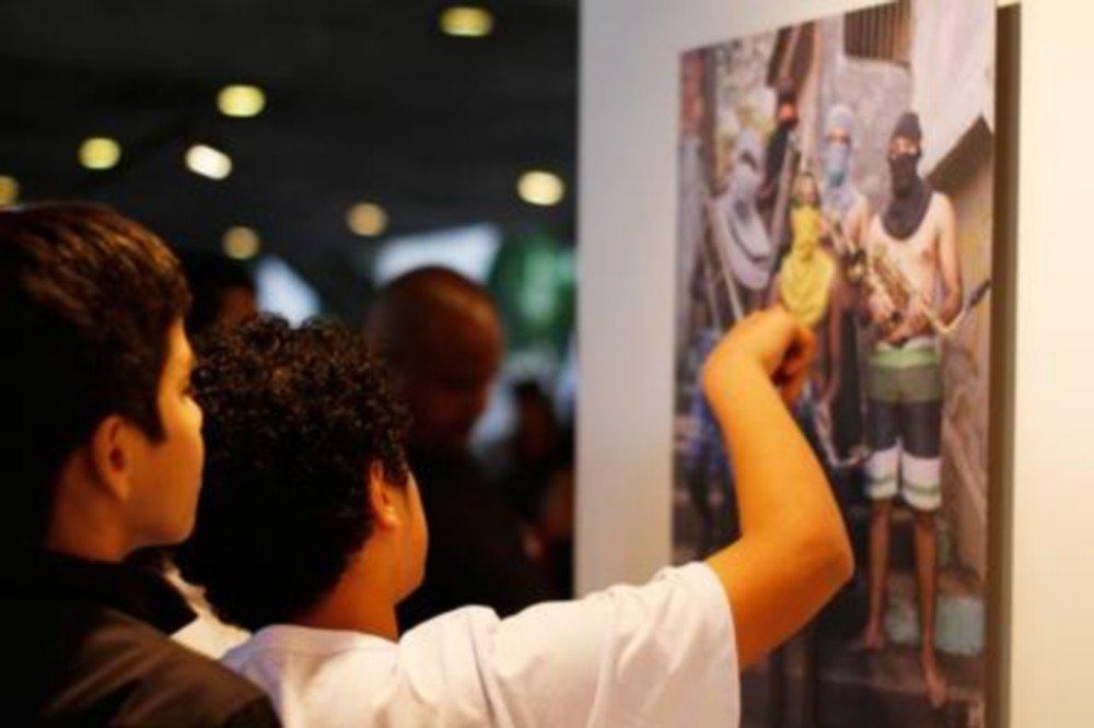 A famosa foto com os jovens mascarados segurando instrumentos musicais como se fossem armas é atração na exposição