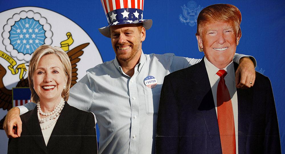 Um homem posa junto às figuras de papelão dos candidatos à presidência norte-americana em 2016, Hillary Clinton e Donald Trump (arquivo)