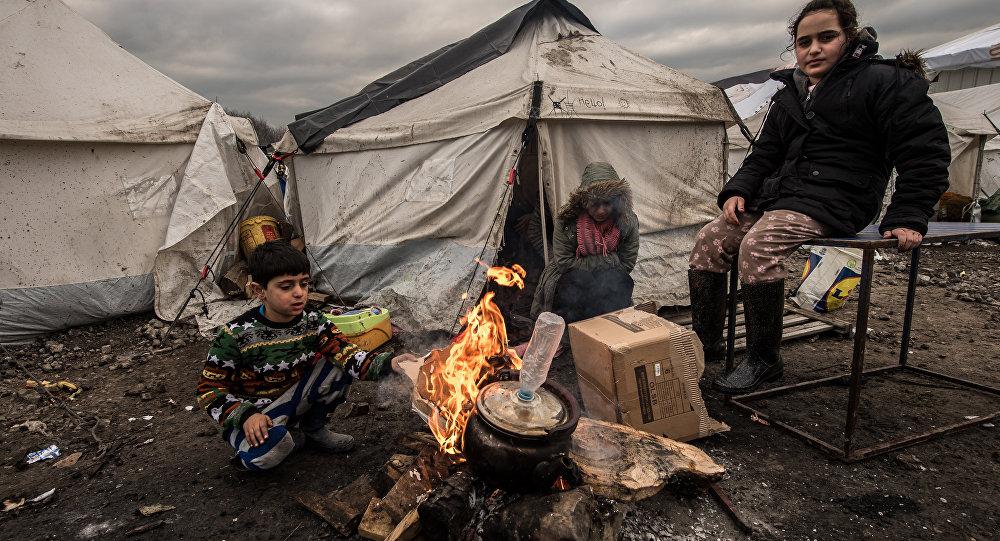 Jovens migrantes se aquecem em torno de um braseiro no campo de migrantes de Grande-Synthe, perto de Dunkirk, em 20 de janeiro de 2016, onde vivem cerca de 2.500 migrantes e refugiados, na sua maioria curdos iraquianos e sírios