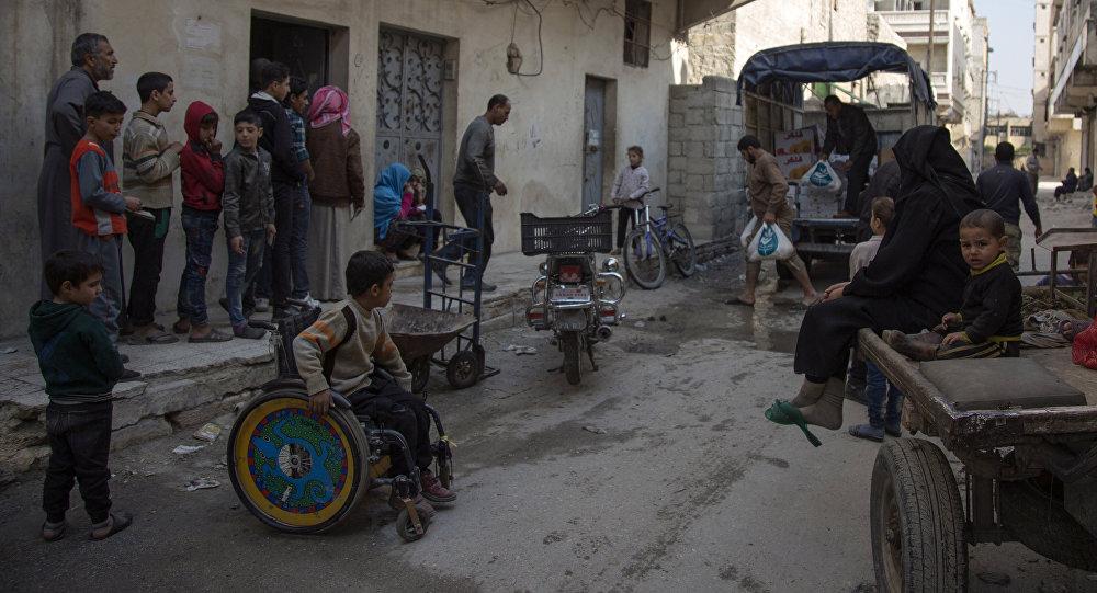 Famílias sírias recebem assistência de fundação humanitária local no bairro de al-Marjah, em Aleppo