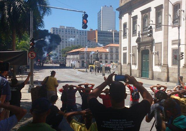 Polícia lança bombas enquanto manifestantes se ajoelham para mostrar que não querem violência