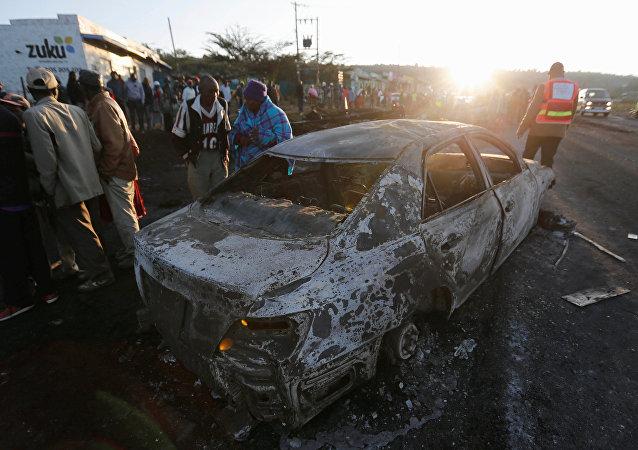 As pessoas olham para os destroços de um carro queimado, perto da cidade de Naivasha, Quênia. Dezembro, 11, 2016.