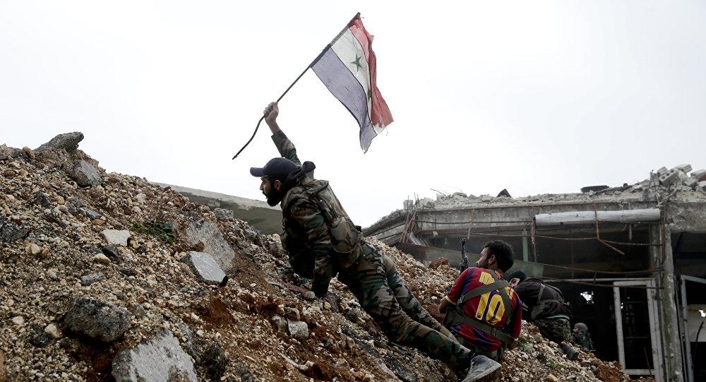Soldado do exército sírio hasteia a bandeira nacional do seu país