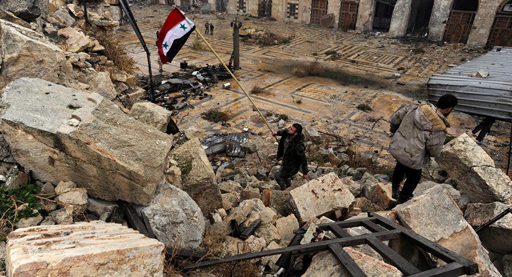 Membro das tropas governamentais hasteia uma bandeira da Síria em Aleppo, 13 de dezembro, 2016