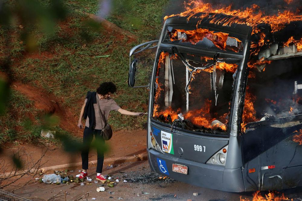 Homem acende cigarro no ônibus em fogo durante manifestações antigovernamentais em Brasília