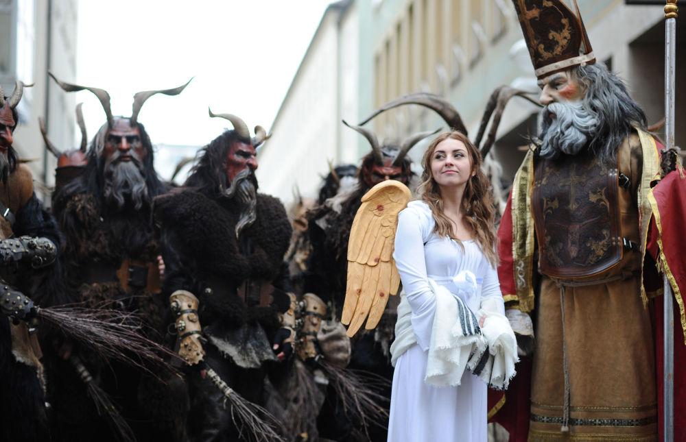 Pessoas vestidas de Krampus, anjo e Papai Noel durante o desfile tradicional de Krampu em Munique, Alemanha