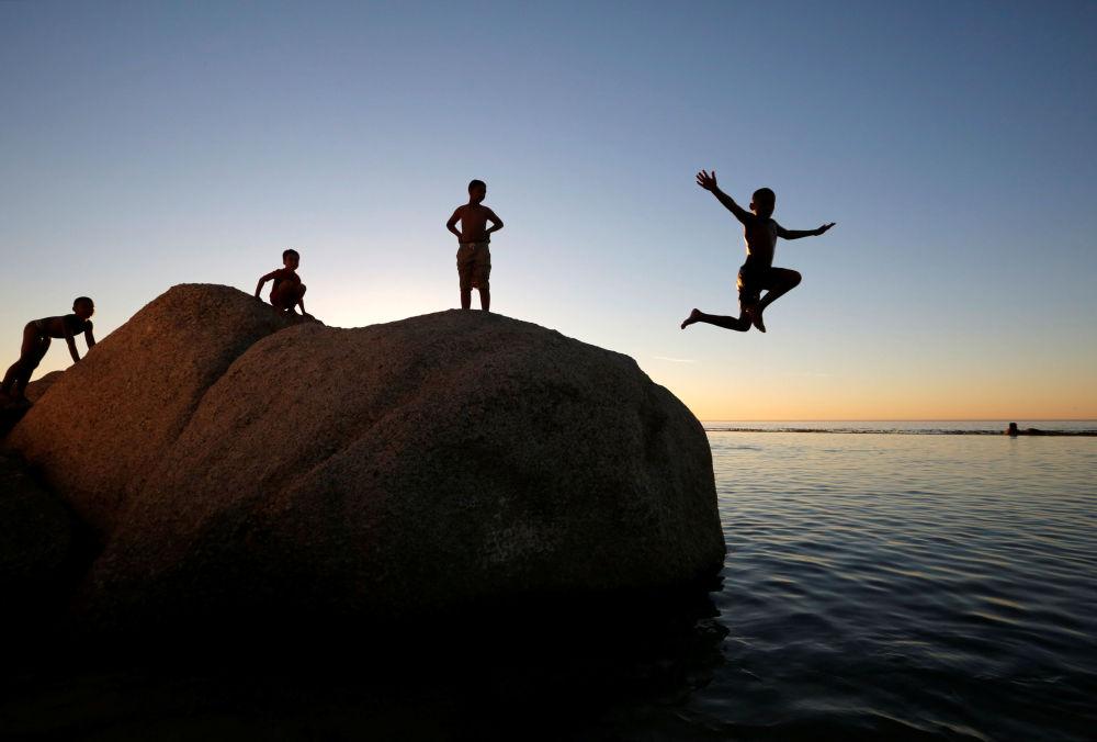 Crianças saltam de uma rocha na Cidade do Cabo, na África do Sul