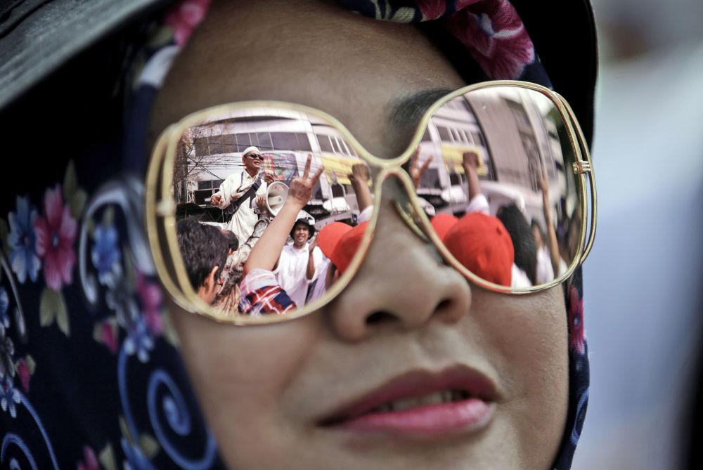 Manifestantes em Jacarta refletidos nas lentes de óculos de uma mulher