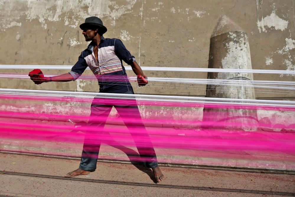 Homem hindu pinta fios para papagaios em rodovia na Índia