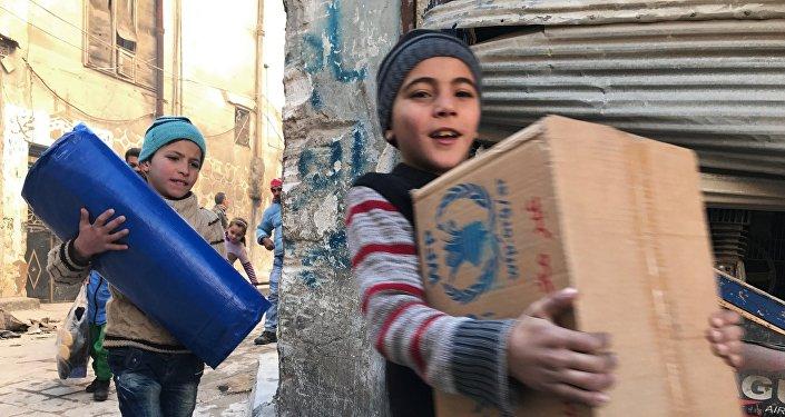 As primeiras crianças a receber a ajuda humanitária russa na parte oriental de Aleppo.