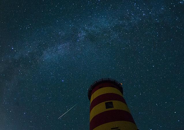 Uma estrela cadente cruza o céu noturno atrás do farol em Pilsum, Alemanha do noroeste