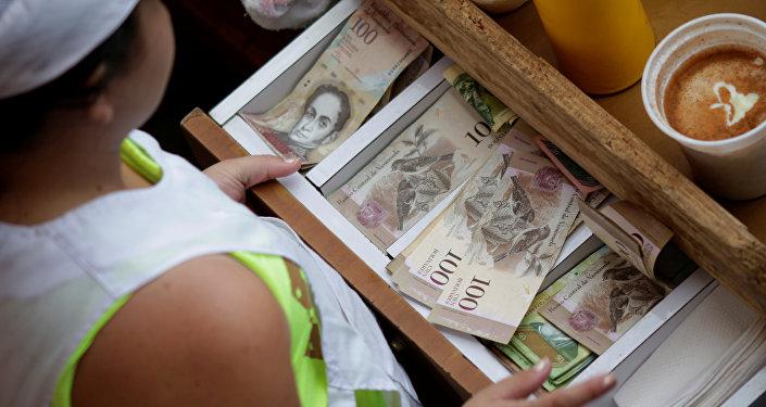Um caixa recebe notas venezuelanas de bolívar em um mercado no centro de Caracas, Venezuela