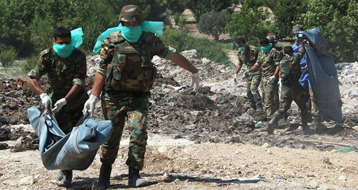 Forças sírias retiram corpos no local de enterramento em massa (foto de arquivo)