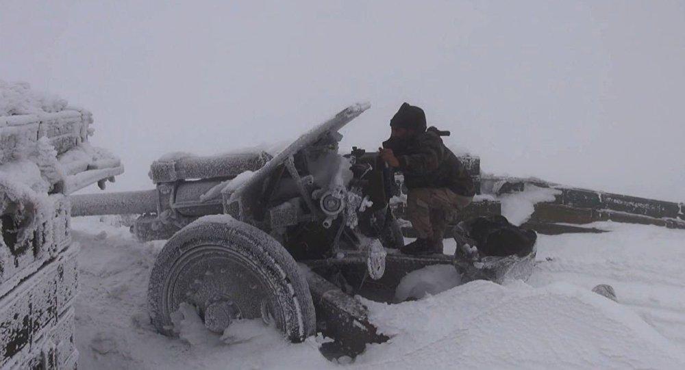 Soldado do exército sírio lança fogo com peça de artilharia coberta de neve, Síria, 26 de dezembro de 2016