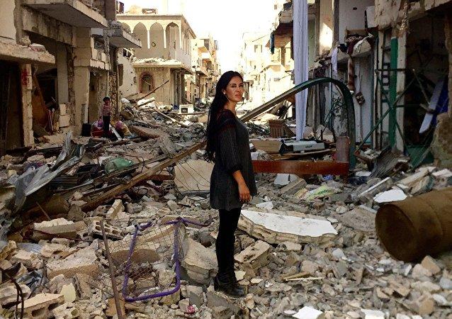 Cineasta boliviana Carla Ortiz em frente às ruinas da cidade síria de Aleppo