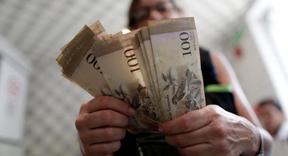 Uma funcionária da caixa está contando bolívares, moeda nacional venezuelana, em um restaurante na capital