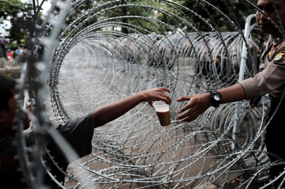 Policial indonésio compra bebida através do arame farpado