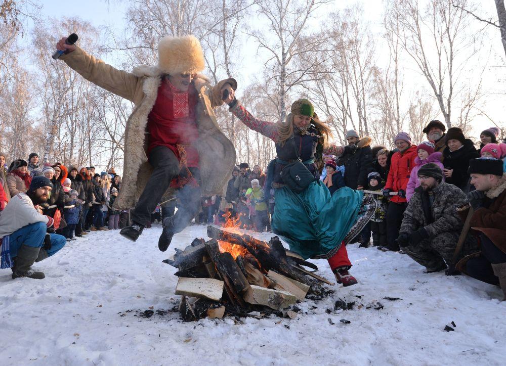 Participantes de festas populares russas saltam por cima de fogueira