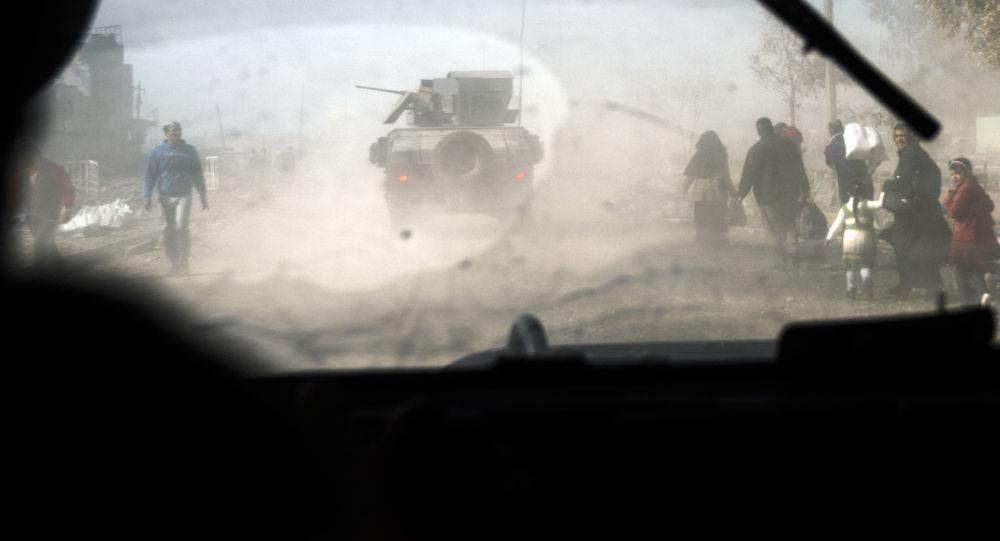 Carros blindados e civis na parte oriental de Mossul