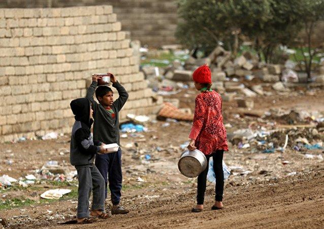 Crianças refugiadas iraquianas, que fugiram de Mossul devido à luta permanente entre as forças iraquianas e os jihadistas do Daesh, em uma rua da aldeia curda de Gogjali, em 2 de dezembro de 2016