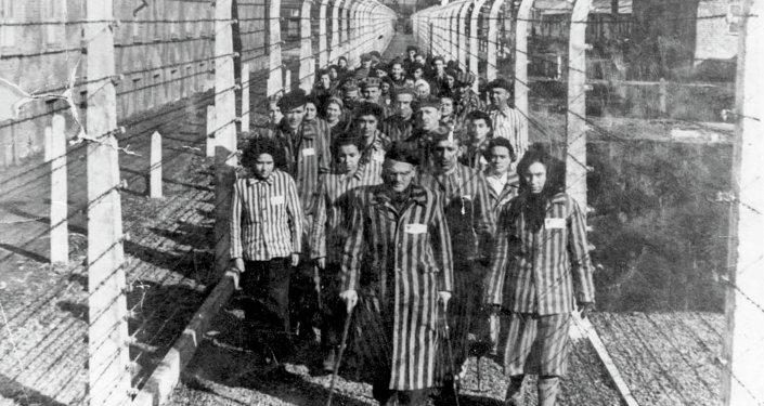 Vítimas do Holocausto marcham por uma das estreitas veredas do campo de concentração de Auschwitz (foto de arquivo)