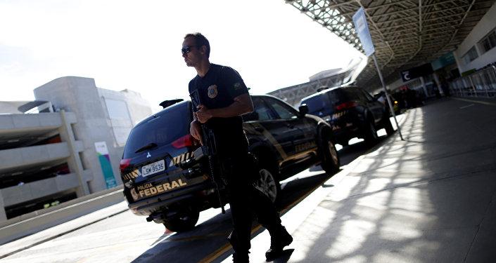 Um agente da Polícia Federal espera no Rio de Janeiro